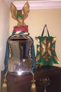 The Prior's arms and crest display on a stechhelm jousting helmet and a targe shield